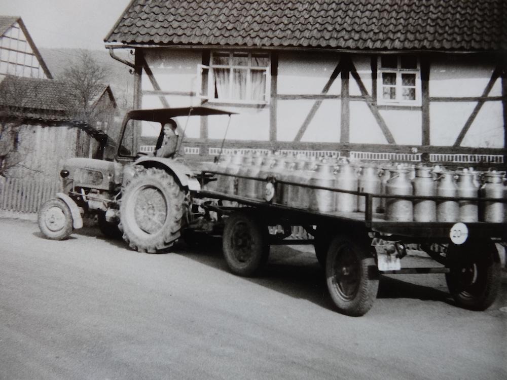 Schwarz-weiß Fotografie eines Traktors mit Dutzenden Milchkannen auf dem Anhänger, ca. 1950er Jahre - Heimat.Museum.Südniedersachsen