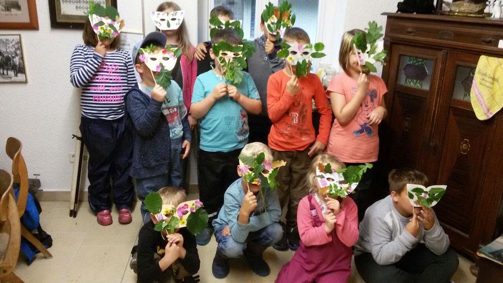Die Kinder präsentieren ihre Waldgeistermasken von der Ferienpassaktion 2017 in Ahlshausen-Sievershausen