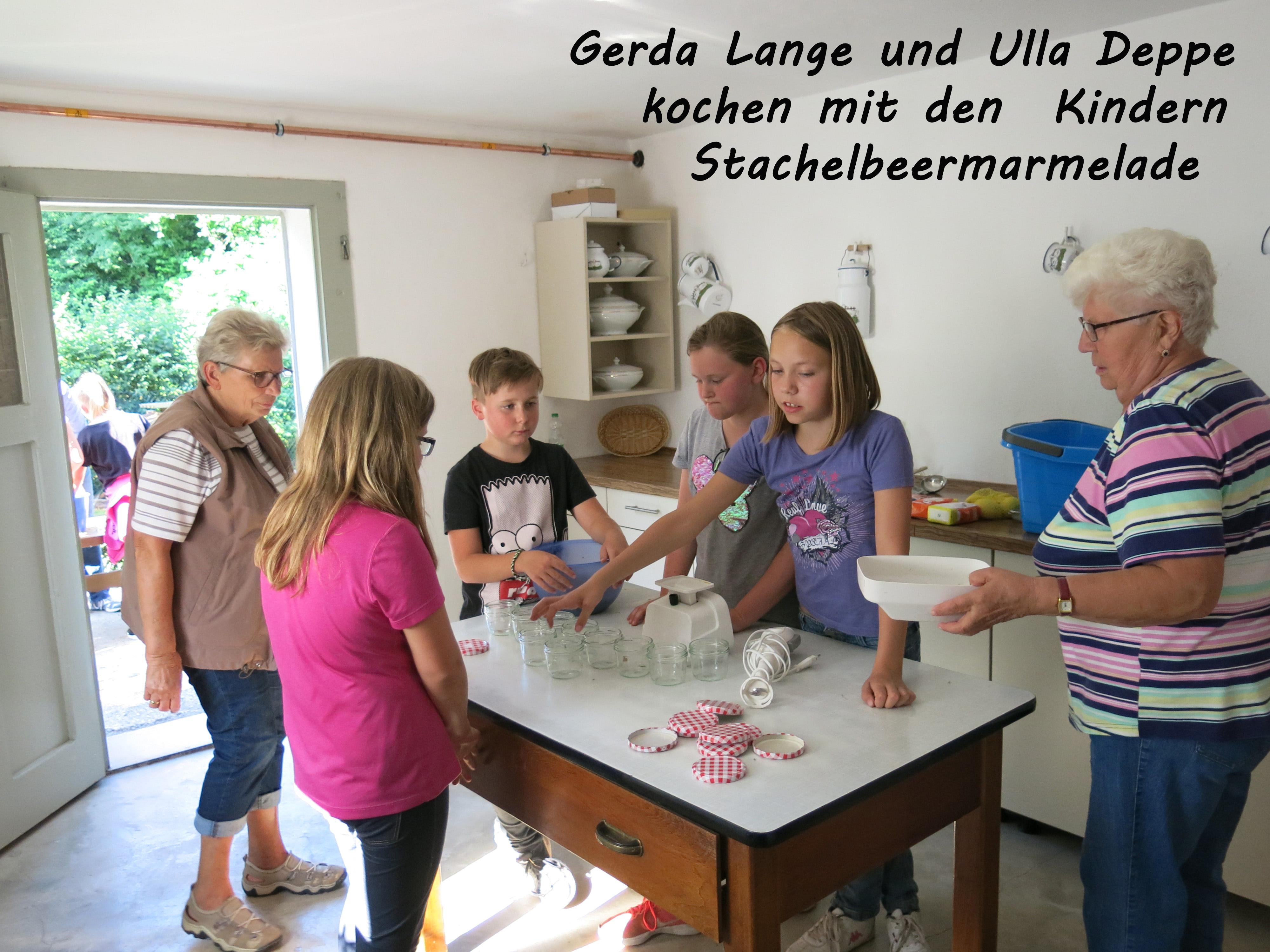 Gerda Lange und Ulla Deppe kochen mit den Kindern Stachelbeermarmelade in der Schweinküche von Hermanns Wohnhaus. Foto: Heimat- und Geschichtsverein Wulften.