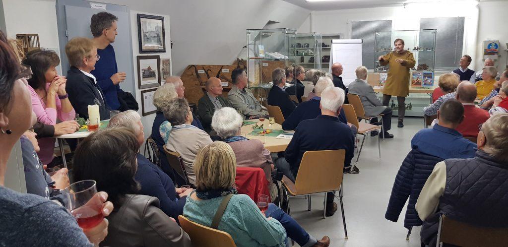 Die Gäste lauschen gebannt dem Vortrag von Dr. Thomas Dahms (vorne) und genießen Wein und Häppchen.