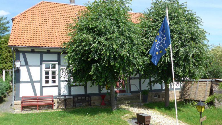 Ein einstöckiges Fachwerkhaus mit einer roten Bank vor dem Gebäude, zwei Bäume umrahmen des Eingang.